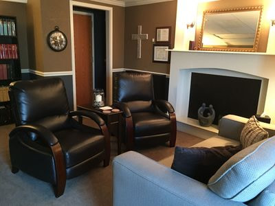 A picture of two leather chairs in front of a fireplace in Dr. Burford's Overland Park office