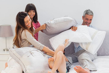 A couple and their daughter have a pillow fight