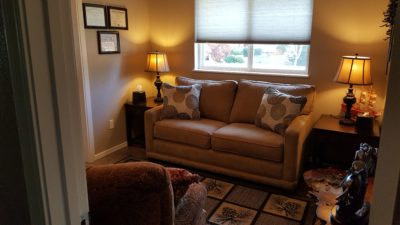A couch in a warmly lit office with pillows on either side