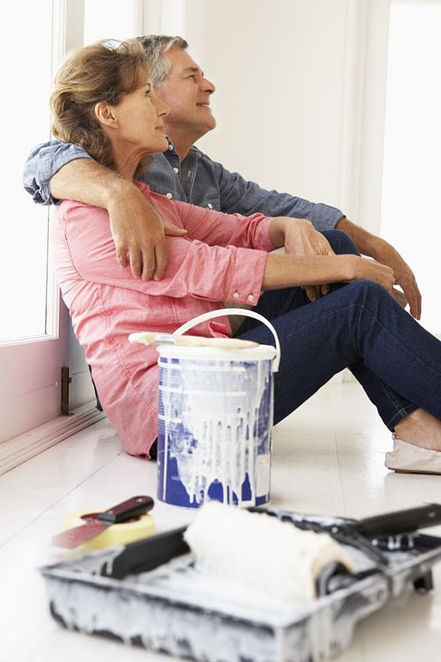 older couple resting on floor with paint bucket, enjoying their work