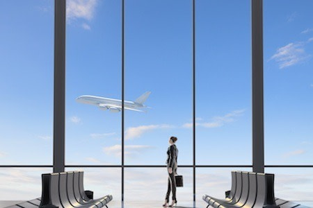 A woman stands in an airport watching a plane take off