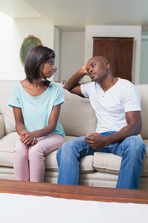 african-american couple on couch looking seriously, but gently at each other