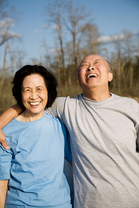 Asian couple laughing arm in arm
