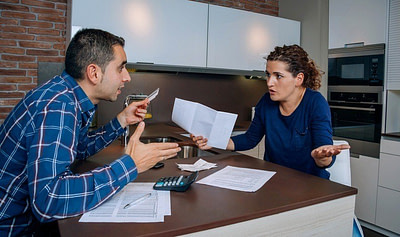 Angry young couple arguing at home by their many credit card debts. Financial family problems concept.