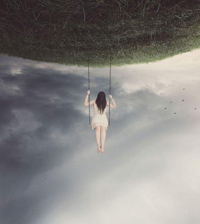 An upside-down landscape with a woman swinging from a swing attached to the land over the sky