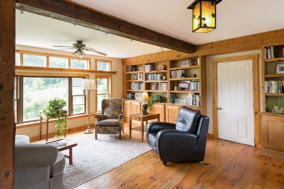 A sunny office with two comfortable chairs and knotty pine walls and flooring