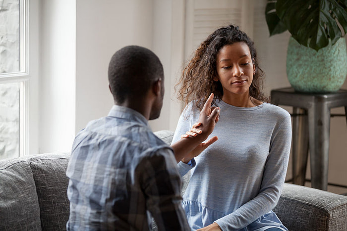 Young mixed race couple sit on couch arguing blaming each other for cheating, black husband and wife fight at home proving point of view, close to divorce or separation. Relationship problem concept