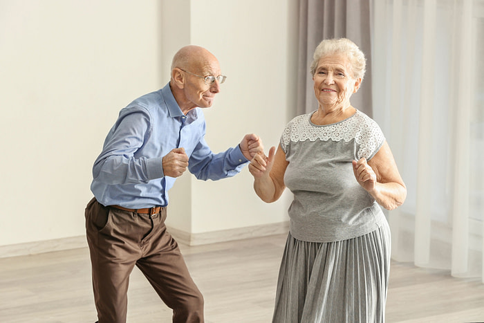 Cute elderly couple dancing at home in a long-term marriage