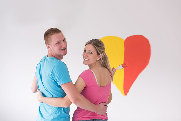 77996665 - young happy couple are painting a heart on the wall while doing repair at home.