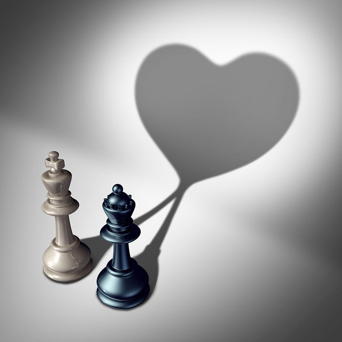 Couple in love as a valentine's day concept as a white king and black queen chess piece casting a united cast shadow coming together in a romantic relationship as a symbol for happy romance and emotional attraction.